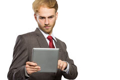 Junger Geschäftsmann mit einem Tabletten-PC, ernster Ausdruck, lokalisiert Stockfotos
