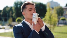 Junger Geschäftsmann mit Geld Ein erfolgreicher Mann ist über Geld glücklich Geld riecht nicht Erfolgreiches Geschäft An geschoss stock video footage