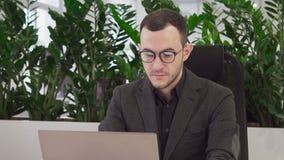 Junger Geschäftsmann mit Gläsern betrachtet den Laptopschirm stock video footage