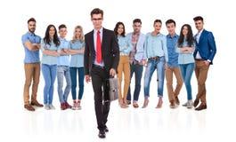Junger Geschäftsmann mit Gläsern tretend vor seiner Gruppe Stockbild