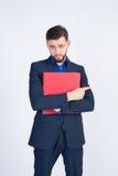 Junger Geschäftsmann mit rotem Ordner Stockbild