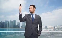 Junger Geschäftsmann mit Smartphone über Stadt Stockbild