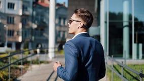 Junger Geschäftsmann mit Sonnenbrille draußen hörend Musik auf seinem Smartphone und dem Tanzen Er gehend nahe Büro stock footage
