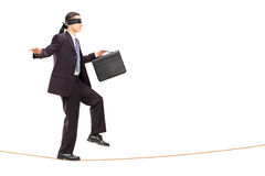 Junger Geschäftsmann mit verbundenen Augen, der auf Seil geht Lizenzfreies Stockfoto