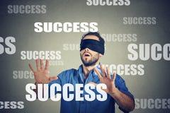 Junger Geschäftsmann mit verbundenen Augen, der nach Erfolg sucht stockbild