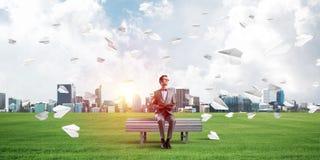 Junger Geschäftsmann oder Student, die Wissenschaft und die Papierflugzeuge herum fliegen studiert stockfotos
