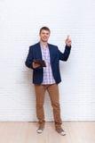 Junger Geschäftsmann-Punkt-Finger, zum des Raumes unter Verwendung des Tablet-Computers zu kopieren Stockfoto