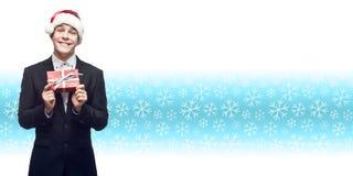Junger Geschäftsmann in Sankt-Hut, der Weihnachtsgeschenk über wint hält Lizenzfreie Stockfotografie