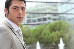 Junger Geschäftsmann schaut beteiligt stockfotografie