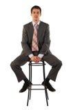 Junger Geschäftsmann sitzt auf Schemel Lizenzfreie Stockbilder
