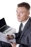 Junger Geschäftsmann sitzt an seinem Schreibtisch Lizenzfreie Stockbilder