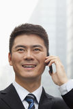 Junger Geschäftsmann Smiling und Unterhaltung am intelligenten Telefon Stockfoto