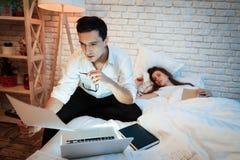 Junger Geschäftsmann studiert Grafiken auf Laptop Auf Bett sind Blätter mit Diagrammen stockfotografie