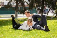 Junger Geschäftsmann und Frau, die Laptop in einer Gleichheit verwendet Stockbilder