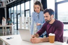 Junger Geschäftsmann und Geschäftsfrau, die mit Laptop im Kleinbetriebbüro arbeitet Lizenzfreies Stockfoto