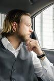 Junger Geschäftsmann und Schauen weg beim Sitzen im Auto Stockbild