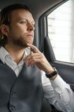 Junger Geschäftsmann und Schauen weg beim Sitzen im Auto Stockbilder