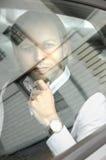 Junger Geschäftsmann und weg schauen durch das Glas beim Sitzen Stockfotografie