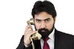 Junger Geschäftsmann unter Verwendung des Weinlesetelefons Stockbilder