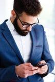Junger Geschäftsmann Using Mobile Phone am Arbeitsplatz stockbild