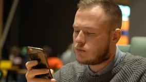Junger Geschäftsmann verwendet Social Networking-Anwendung auf seinem Smartphone stockbilder