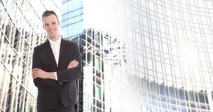 Junger Geschäftsmann vor unscharfem Bürogebäudehintergrund Lizenzfreie Stockfotos