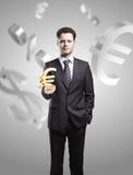 Junger Geschäftsmann wählt ein Goldeuro-Zeichen Stockfotos