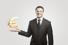 Junger Geschäftsmann wählt ein Goldeuro-Zeichen. Stockfoto
