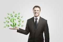 Junger Geschäftsmann wählt Zeichen eines grüne US-Dollars Stockfotografie