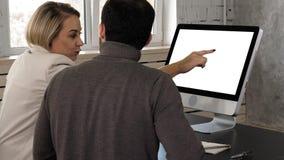 Junger Geschäftsmann zwei, der eine Sitzung im Büro schaut im Monitor hat Weiße Bildschirmanzeige lizenzfreie stockfotografie