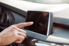 Junger Geschäftsmannfahrer, der innerhalb Auto touchign Schirmes der Bedienfeldnahaufnahme sitzt stockfotografie