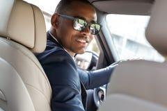 Junger Geschäftsmannfahrer in der Sonnenbrille, die innerhalb des Autofahrens sitzt, Rücksitz-Ansichtnahaufnahme der Kamera zurüc stockbild
