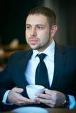 Junger Geschäftsmanngetränktee am Café stockfotos