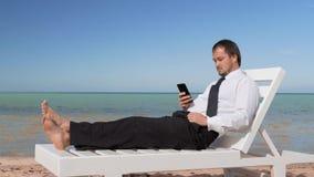 Junger Gesch?ftsmann arbeitet an dem Strand M?nnlicher Fachmann sitzt im bequemen Ruhesessel stock video footage