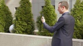 Junger Gesch?ftsmann, der hinunter die Stra?e und eine Mitteilung auf den Smartphone schreiben geht stock video