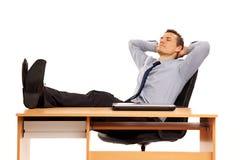Junger Geschäftsmann, der bei der Arbeit sich entspannt. Stockfotos