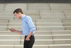 Junger Geschäftsmann, der draußen geht und Handy betrachtet Lizenzfreie Stockfotos