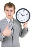 Junger Geschäftsmann, der eine Borduhr anhält Lizenzfreies Stockfoto