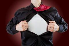 Junger Geschäftsmann, der eine Superheldklage aufdeckt Lizenzfreie Stockfotos
