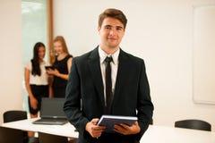 Junger Geschäftsmann, der in erstem einfachem mit Mitarbeitern in b steht Stockfotografie