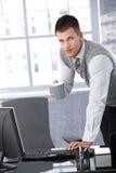 Junger Geschäftsmann, der mit Computer arbeitet Stockbild