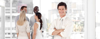 Junger Geschäftsmann, der mit Geschäftsteam lächelt Stockfotografie