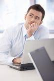 Junger Geschäftsmann, der am Schreibtisch träumt Stockfotos