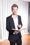 Junger Geschäftsmann des Porträts in der Klage, die Kenntnisse in Buch nimmt Lizenzfreie Stockfotografie
