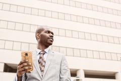 Junger Geschäftsmann mit Handy draußen Stockbild
