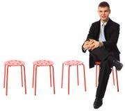 Junger Geschäftsmann sitzt auf rotem Schemelfahrwerkbein auf Fahrwerkbein Stockbild