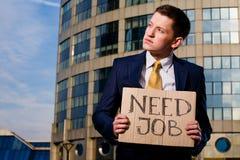 Junger Geschäftsmannholdingzeichen Notwendigkeits-Job draußen Stockbilder