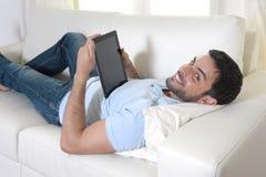 Junger glücklicher attraktiver Mann, der die digitale Auflage oder Tablette sitzen auf Couch verwendet Stockfoto