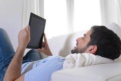Junger glücklicher attraktiver Mann, der die digitale Auflage oder Tablette sitzen auf Couch verwendet Lizenzfreie Stockbilder