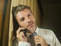 Junger glücklicher attraktiver und entspannter Geschäftsmann, der zu Hause mit dem Handylächeln nett oder Büro in erfolgreichem s stockbild